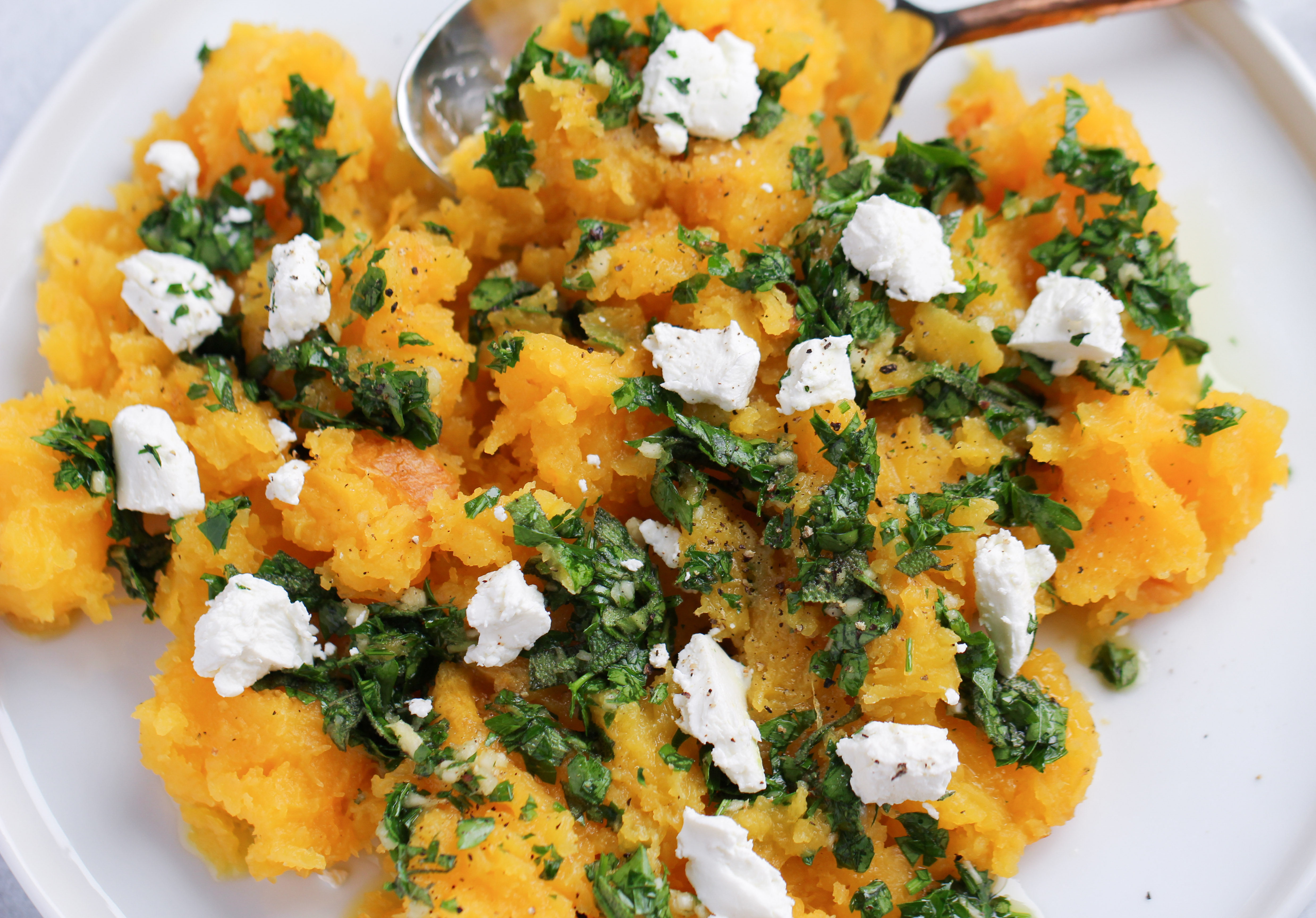 Butternut squash in herb oil and goat cheese on a white plate